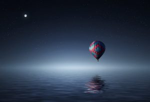 Dreamy image of hot air balloon floating above water in the night sky