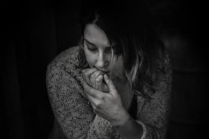 Black and white photo of woman looking anxious biting on her fingernails
