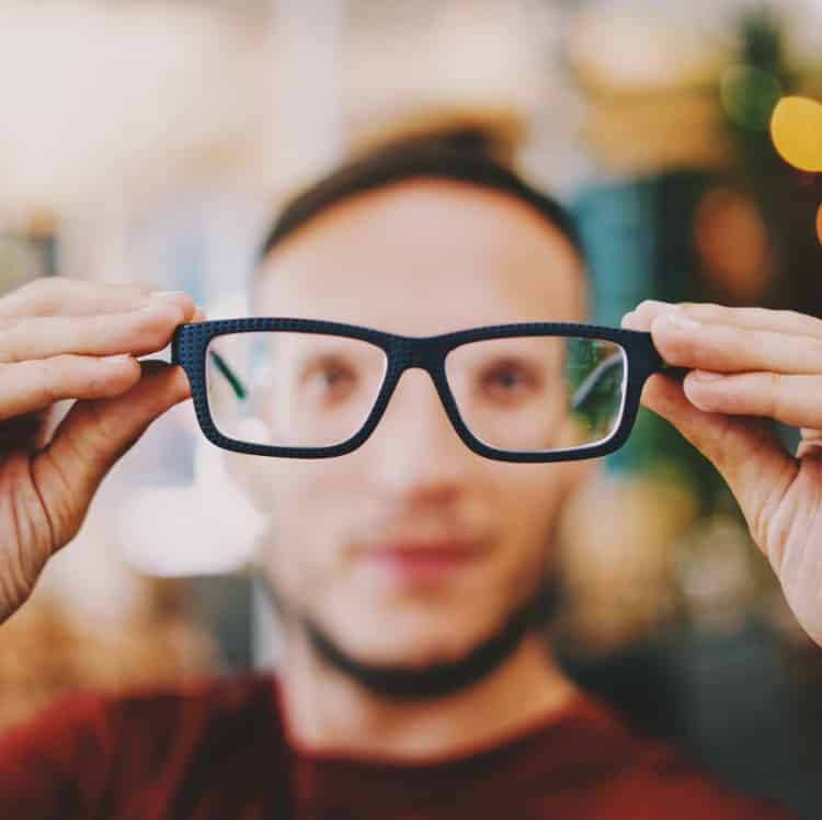 blurry male face seen through extended eye glasses