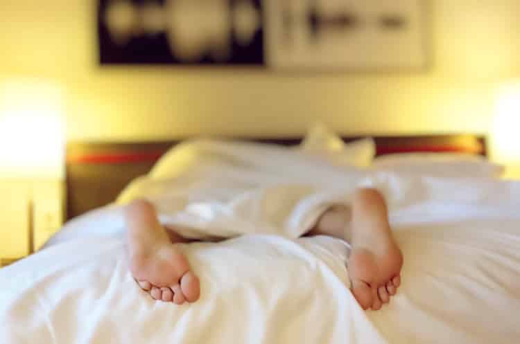 Person sleeping soundly with feet sticking out of bed