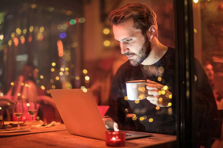 Man drinking coffee while working on his computer late at night