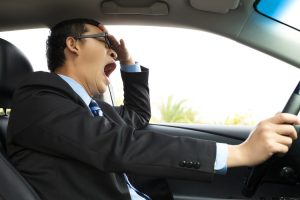 Exhausted driver yawning while at the wheel of a car