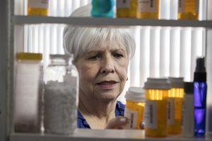 Older woman examines bottle of prescription medication pulled from medicine cabinet