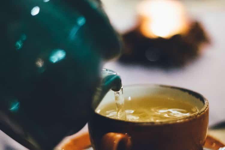 Tea pot pouring tea into a cup