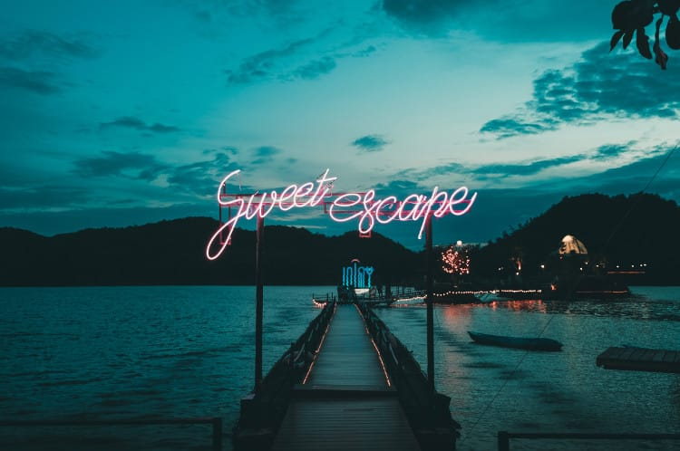Sweet escape neon sign in front of dock at sunset