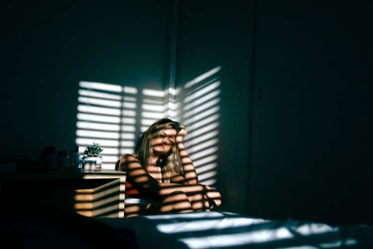 Exhausted woman crouching in corner of darkened room
