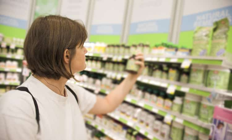 Woman looks at bottle of natural supplement in health food store