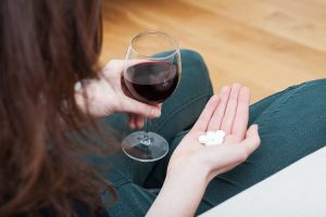 Woman holding a glass of red wine and white sleeping pills