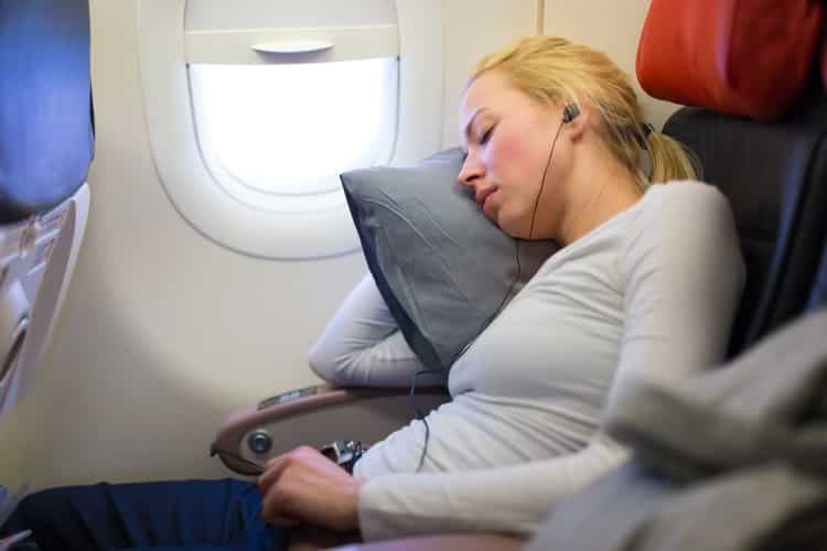 Woman sleeping fitfully on an airplane