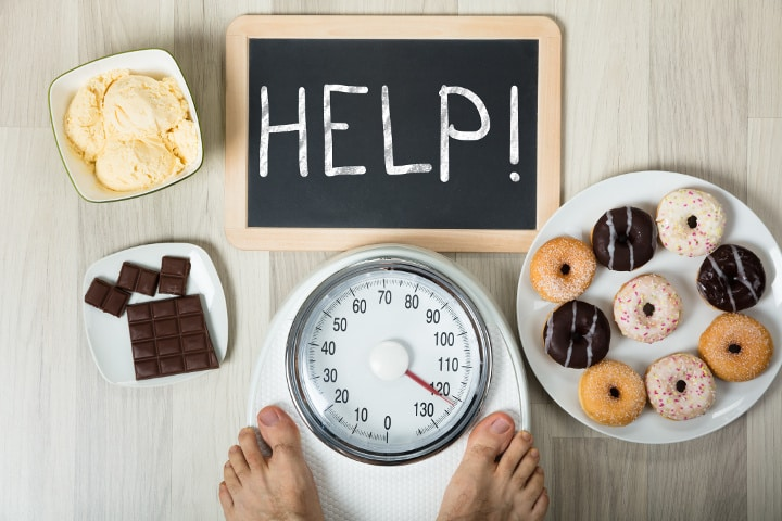 Man on scale tempted by sugary foods with sign for help