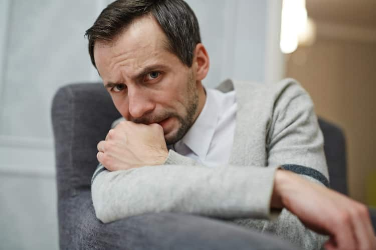 Anxious man biting on finger nail in therapy session