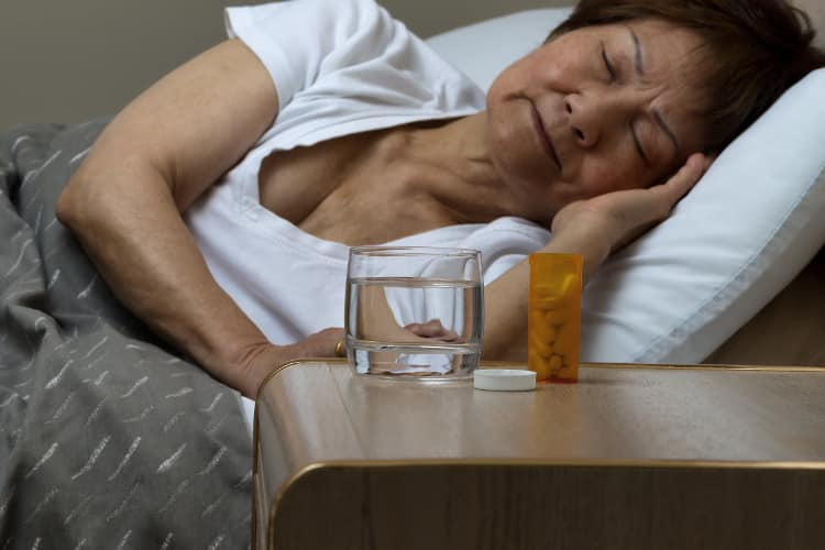 Asian woman sleeping with pills and glass of water next to bed