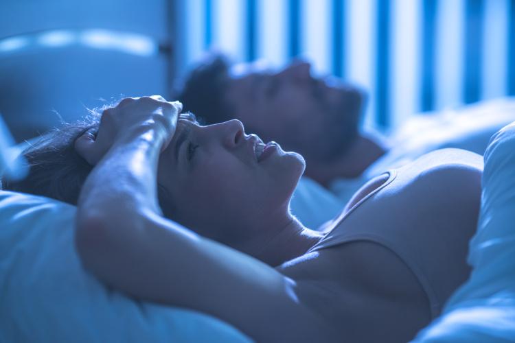 Women awake in bed next to sleeping partner