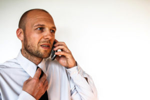 Worried man speaking on cell phone while loosening his tie