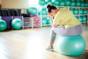 Distraught woman on yoga ball in workout studio