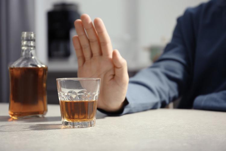 Man pushing away glass of whiskey