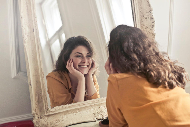 Happy woman looking at her reflection in a mirror