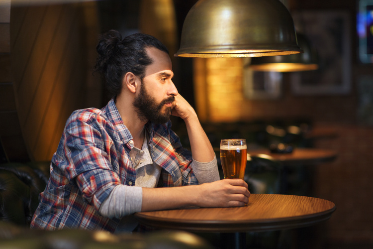Man drinking beer in a bar all alone