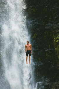 Man calmly jumping off of waterfall