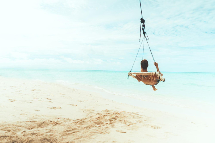 Man relaxing in hanging chair by tropical seashore