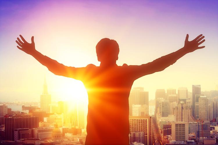 Man on skyscraper celebrating the sunrise