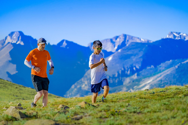 Older man and younger boy running on mountain trail