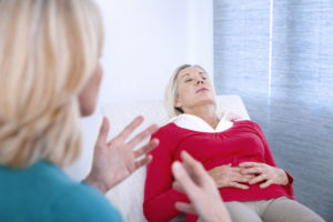 Woman undergoing hypnosis at therapist's office