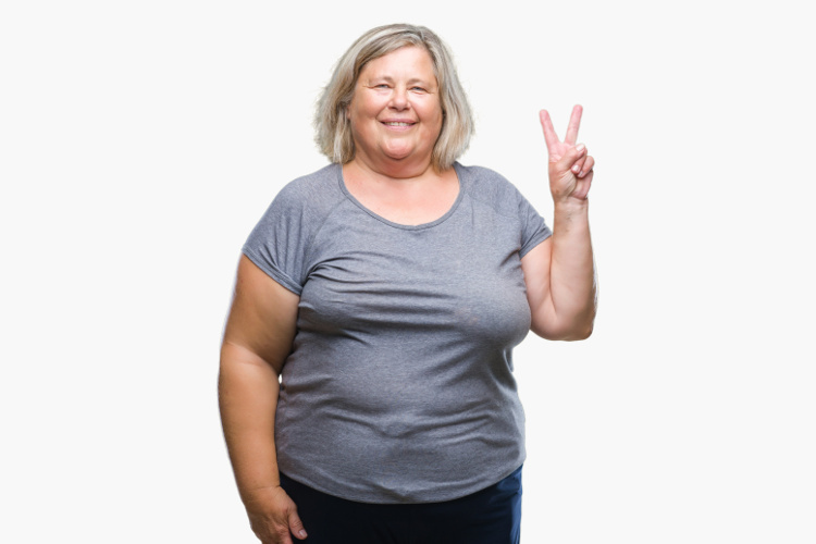 Overweight woman in grey T shirt giving the peace sign