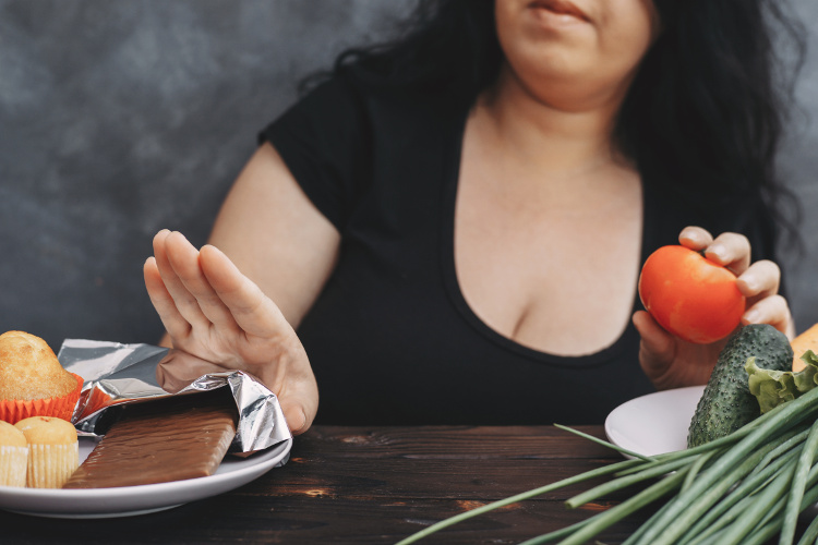 Overweight woman pushing away snacks in favor of vegetables