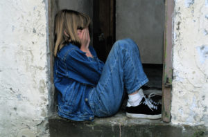 Young girl with hands over her face hiding in a doorway