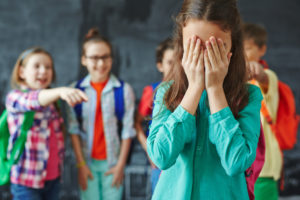 Young schoolgirl in tears getting mocked by her classmates