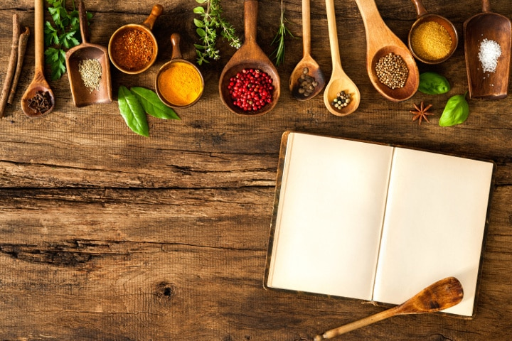 spoons filled with ingredients on table with cookbook