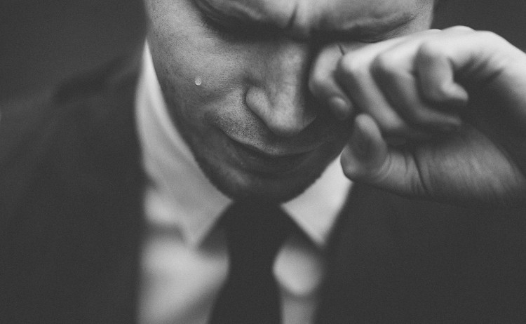 Man in business suit wiping tears from his eyes