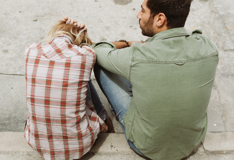 Man sitting next to despondent woman on a curb
