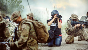War correspondent taking pictures among soldiers in combat