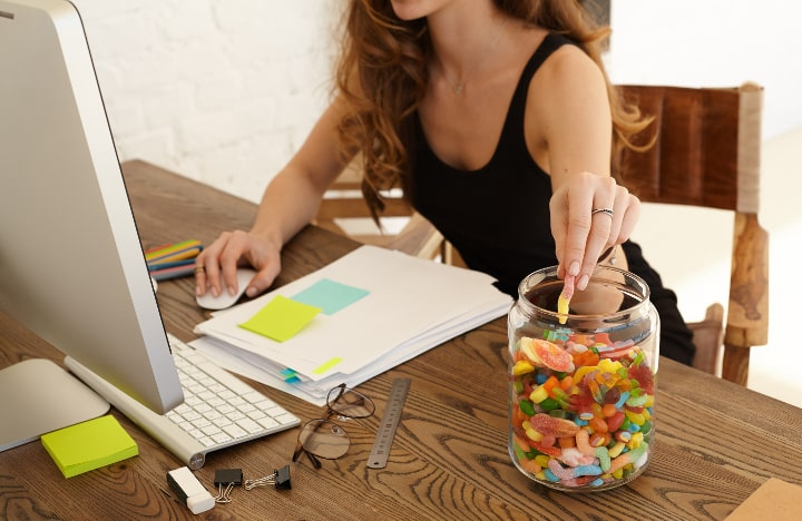 woman at work snacking from candy jar