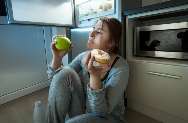 woman choosing between an apple and donut for a meal