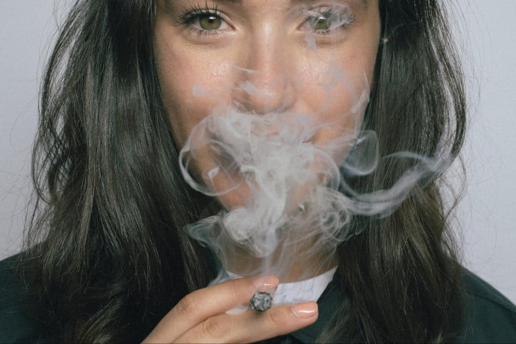 Dark haired woman blowing smoke from cigarette