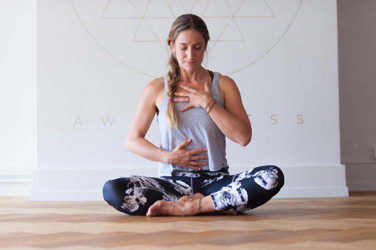 Woman in yoga studio focusing on deep breathing exercises