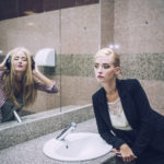 Woman in front of bathroom mirror with her alter ego in the reflection