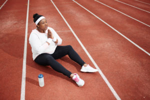 Woman giving gratitude on track before workout