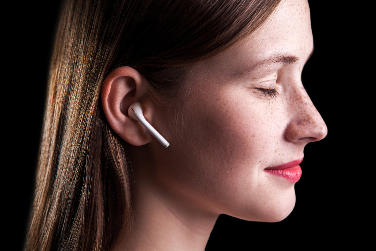 Woman listening to hypnosis audio through wireless earbuds