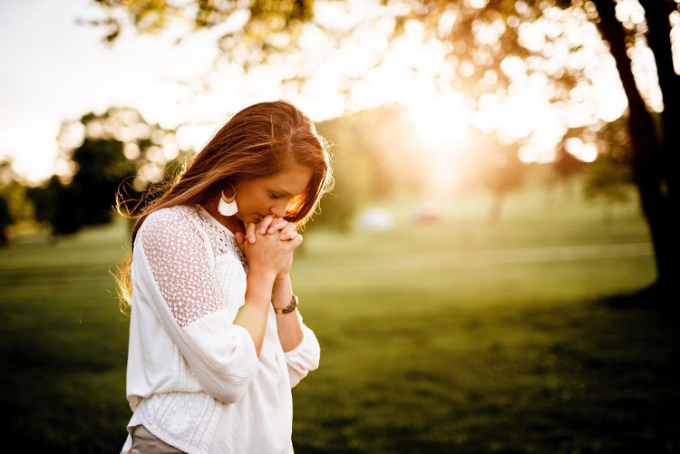 Young woman prayerfully giving gratitude in field at sunrise